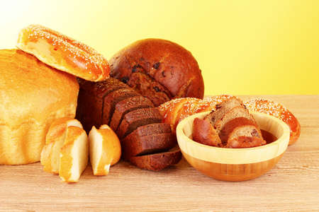 Baked bread assortment on yellow background photo