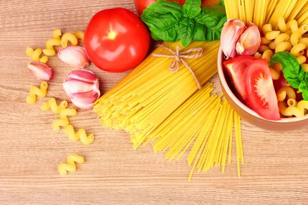spaghetti with garlic, onion, spices  and basil on a yellow background photo