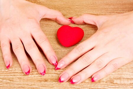 red heart in hands on wooden background photo