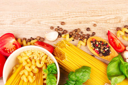 spaghetti with garlic, onion, spices  and basil on a yellow background Stock Photo - 9384688