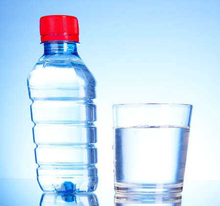 Bottle of water and glass on blue background photo