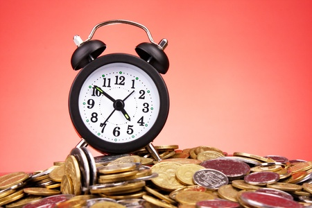 Alarm clock and coins on red background Stock Photo - 9453435