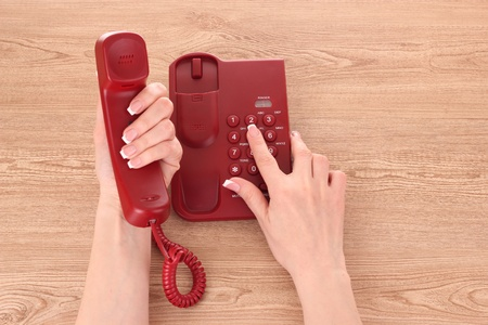 red phone and hands on wooden table Stock Photo - 9453234