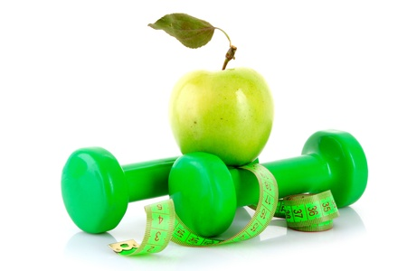 Dumbbells, green apple and measuring tape  isolaeted on white photo