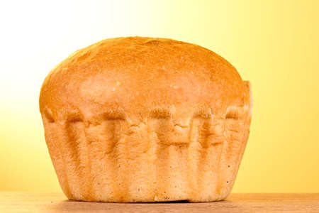 Fresh wheat bread on yellow background photo