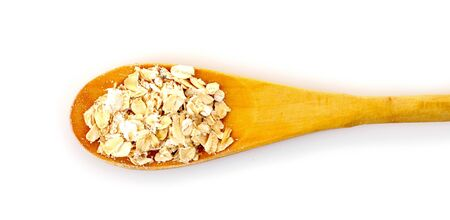 Uncoocked rolled oats in wooden spoon isolated on white photo
