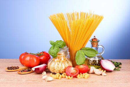 spaghetti with garlic, onion, spices and basil on a yellow background
