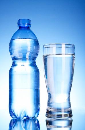 agua purificada: Botella de agua y vidrio sobre fondo azul