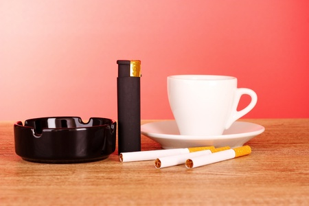 Cigarettes, ashtray and cup of coffee on red background photo