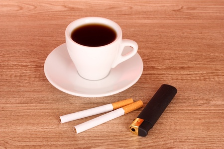 Cigarettes and cup of coffee on wooden background photo