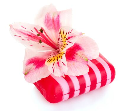 Pink flower and soap isolated on white photo