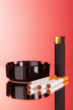Cigarettes, ashtray and lighter on red background photo