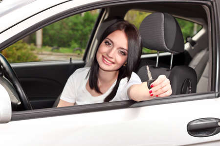 pass test: young brunette woman with keys to new car