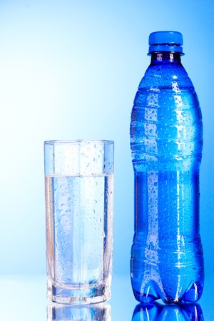 Bottle of water with glass on blue background photo