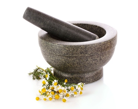 Mortar and pestle with flowers isolated on white photo
