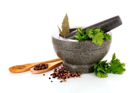 Mortar and pestle, parsley, bay leaf and pepper isolated on white Stock Photo