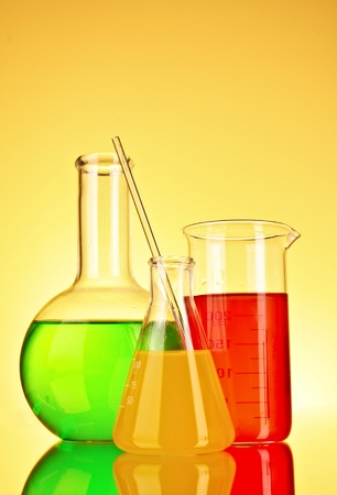 milliliters: Laboratory glassware on yellow background Stock Photo