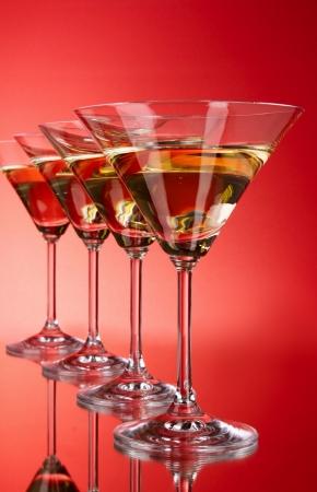 copa martini: Cuatro copas de martini sobre fondo rojo Foto de archivo
