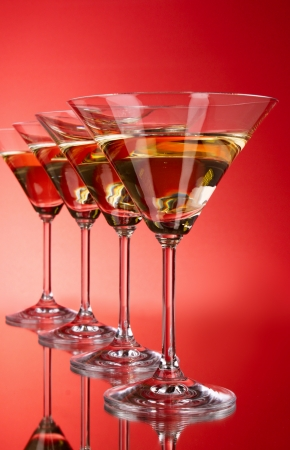 Four martini glasses on red background