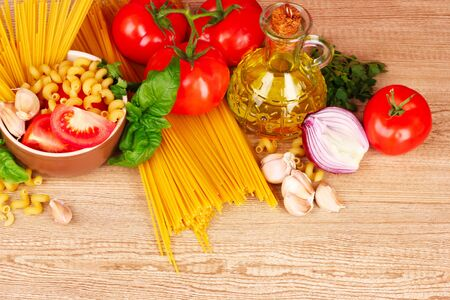 spaghetti with garlic, onion, spices  and basil on a yellow background Stock Photo - 9660027