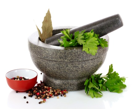Mortar and pestle, parsley, bay leaf and pepper isolated on white Stock Photo - 9694235