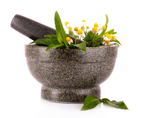 mortar and pestle: stone pestle and mortar with chamomile and mint isolated on white
