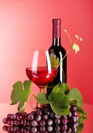 Wine bottle and glass on red background Stock Photo - 9715401