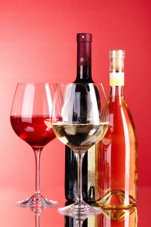 Wine bottle and glass on red background Stock Photo - 9715362