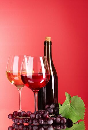 Wine bottle and glass on red background Stock Photo - 9715363