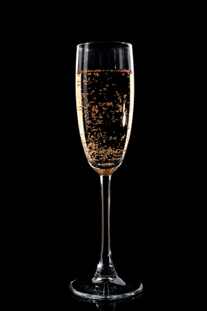 Glass with champagne on black background photo