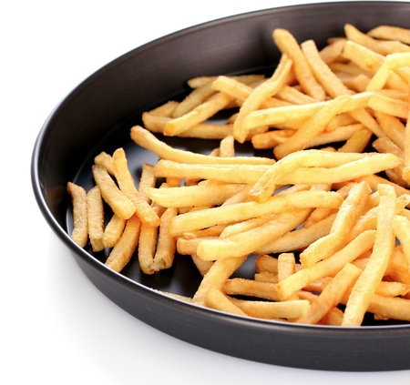 French fries in the pan isolated on white photo