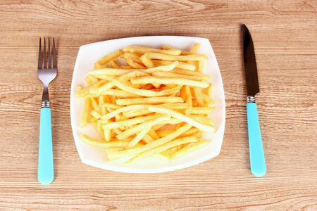 French fries on a plate and cutlery on a wooden background photo