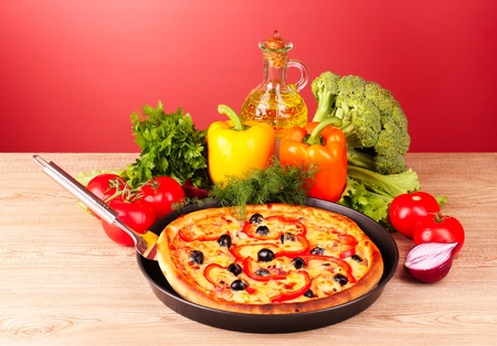 pizza and vegetables on a red background photo