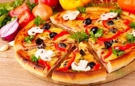 rebanada de pizza: Pizza y verduras sobre fondo de madera