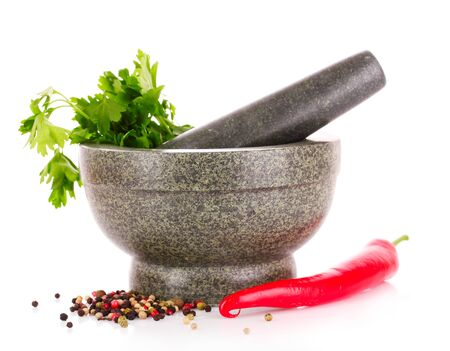 herbalist: parsley in amortar gray and red pepper isolated on white
