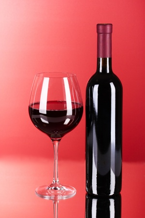 Wine bottle and glass on red background Stock Photo - 9785260