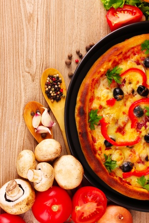 pizza and vegetables on a wooden background photo