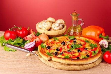 pizza and vegetables on a red background