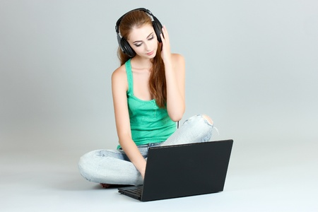 beautiful young girl in headphones with a laptop on a gray background Stock Photo - 10410018