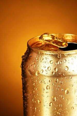 inhibited: gold tin can on a yellow background. Focus on nearest water drops