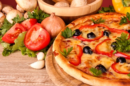 tasty pizza with olives and vegetables on a wooden background photo