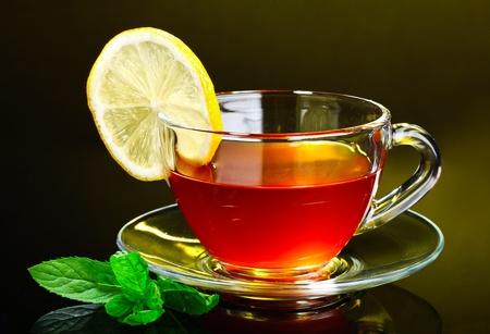 amarillo y negro: agradable taza de té y menta sobre fondo amarillo Foto de archivo
