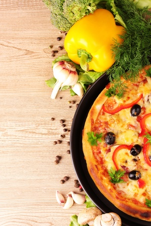 european food: pizza and vegetables on a wooden background