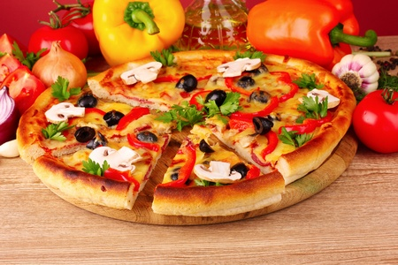 pizza and vegetables on wooden background photo