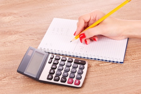 hand, notepad and calculator on wooden background photo
