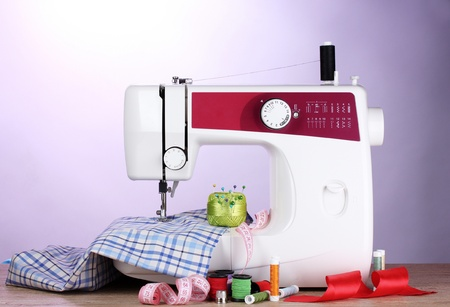 sewing machine and fabric on purple background photo