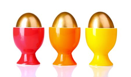 golden eggs in bright stands isolated on white photo