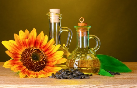 sunflower oil and sunflower on yellow background photo