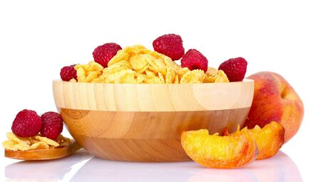 tasty cornflakes and fruit in wooden bowl isolated on white photo
