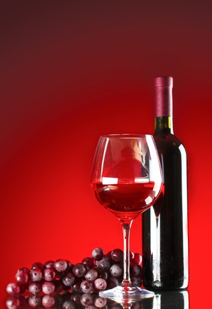 bottle of wine glasses and grapes on red background photo